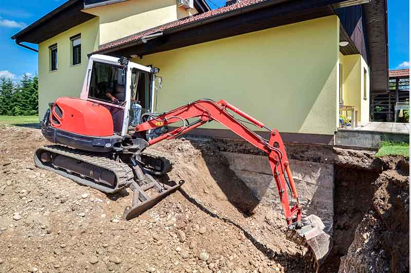 Heavy machinery performing excavation outside a home